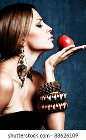 woman with oriental jewelry hold an apple, profile, studio shot