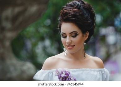 Woman with original make-up and tall hair-do holds violet flower