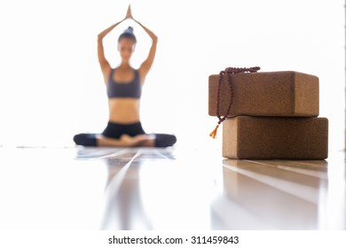 Woman out of focus practicing yoga, in focus two blocks and a mala for meditation.