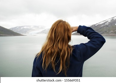 A Woman in Outdoor Look Watches at Glaciers in the Mountains