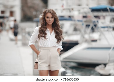 woman outdoor portrait. fashion and beauty in the city street. long healthy hair and cheerful smile