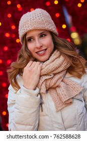 Woman outdoor in winter. Young happy woman dressed for winter in front of christmas lights.