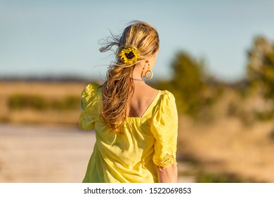 Woman outdoors in beautiful sunshine rural area.  She has a sunflower in her long wavy hair blowing gently in the wind.