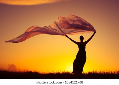 Woman outdoors in dress holding a long fabric blowing in the wind. Freedom and serenity concept.