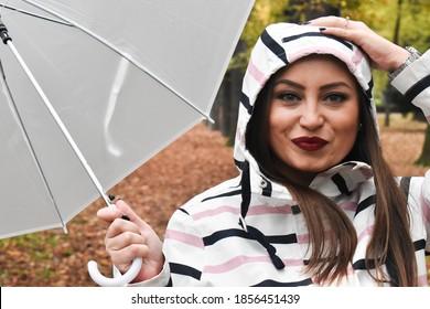 Woman outdoors, holding  white umbrella, autumn