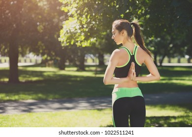 Woman outdoors making asana exercises. Girl doing Reverse Prayer Pose, back and shoulders stretching. Wellness, calmness, relax, healthy, active lifestyle concept