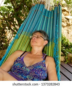 Woman outdoors sleeping in a Hammock with green tree in the background