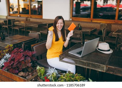 Woman in outdoors street cafe sitting at table with modern laptop pc computer hold in hand bank credit card, passport, book online airplane ticket. Restaurant in free time. Lifestyle business concept