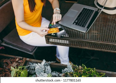 Woman in outdoors street coffee shop sitting with laptop pc computer, hold wireless modern bank payment terminal to process acquire credit card payments. Mobile Office in free time. Freelance concept