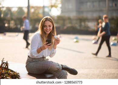 Woman outdoors use cell phone while having chocolate bar