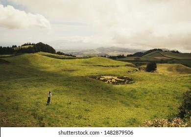 Woman outdoors walking in summer field, beautiful landscape skyline in Azores, Portugal