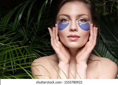 Woman with outstanding natural hair applying special cosmetological utensils for facial dermis to remain clean and fresh. Gorgeous female relax in spa. Skincare concept