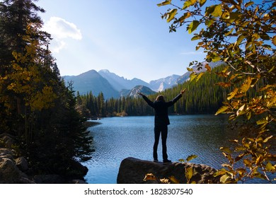 Woman with outstretched arms at Bear Lake in Rocky Mountain National Park