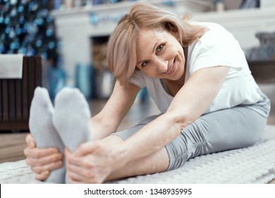 A Woman Over 50 Years Old Enjoys Yoga. She Took the Position of Asana on the Floor. Woman Loves to do Yoga at Home. Close Up Shot.