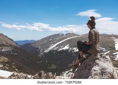 Woman overlooking a mountainous vista point.
