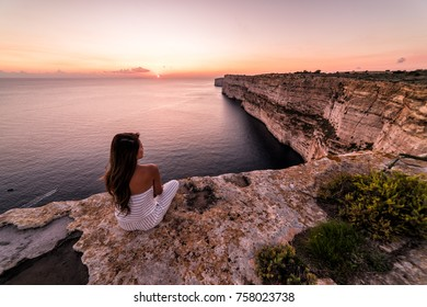Woman overlooks the famous Ta Cenc Cliffs at sunset.  These cliffs on the island of Gozo overlook the Mediterranean Sea.  Country of Malta.