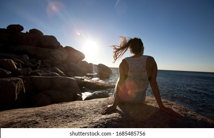 Woman overlooks sunny bay during a summer evening as the sun goes down in llandudno, Cape town, South Africa.