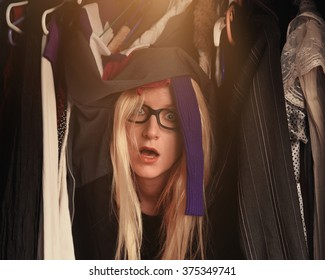 A woman is overwhelmed in a closet of messy clothes with glasses for a style or fashion concept.