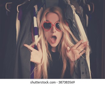 A woman is overwhelmed in a closet of messy clothes with red glasses for a style or fashion concept.