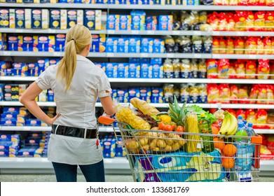Eine Frau ist beim Einkaufen mit dem breiten Angebot im Supermarkt überfordert.