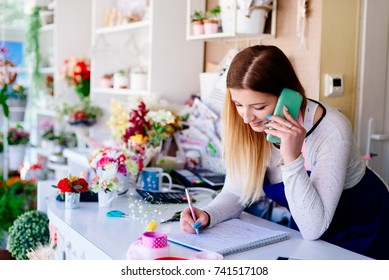 Woman owner of florist shop taking orders by phone