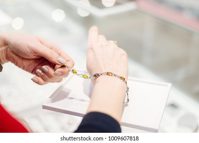Woman owner of jewelry shop presenting silver bracelet with amber. Customer service in jewelry store.