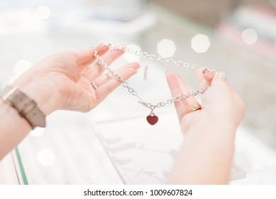 Woman owner of jewelry shop presenting silver necklace with amber. Customer service in jewelry store.