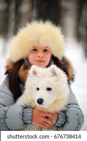 Woman owner with white Samoyed dog lying on snow in winter day