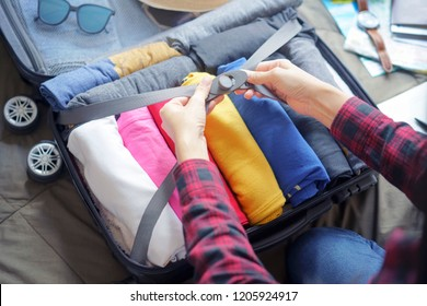 Woman pack clothes in suitcase bag on bed, prepare for new journey and travel to long weekend trip.