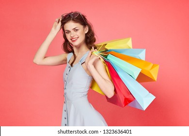 woman with packages on a pink background