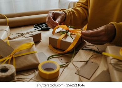Woman packaging box. Kraft wrapping paper and natural twine. Recycling material. Happy holiday present, surprise. Gifts for boxing day. Delivery service, shipping. Handwork art craft. Celebration