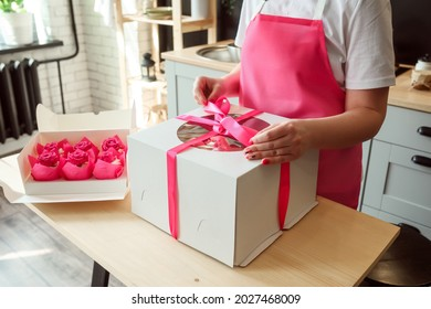 Woman is packing big birthday cake into a box, pink cupcakes in the package on the box. Desserts delivery concept.