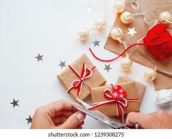 Woman is packing Christmas and New Year DIY presents in craft paper. Gifts tied with white and red threads. Boxes and star confetti on white background.