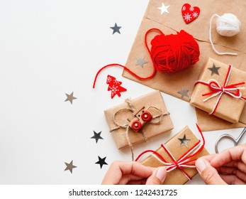 Woman is packing Christmas and New Year DIY presents in craft paper. Gifts tied with threads. Boxes, red heart and Christmas tree symbols on white background.