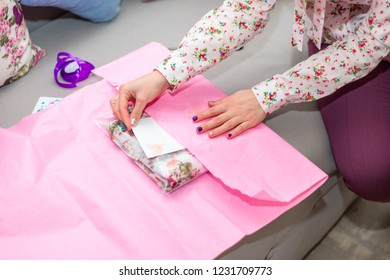 A woman is packing a gift in a pink wrap while sitting on a sofa. Gifts, holiday, new year, christmas.