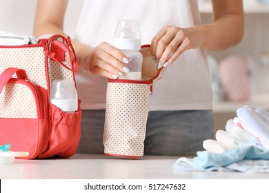 Woman packing her bag with child bottle