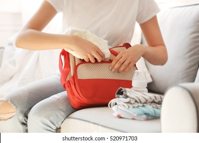 Woman packing her bag with child stuff on couch