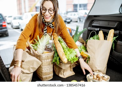 Woman packing shopping bags with fresh food into the car trunk, view from the vehicle interior