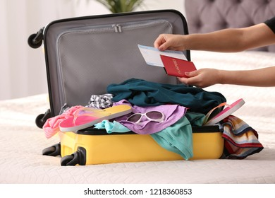Woman packing suitcase for journey at home