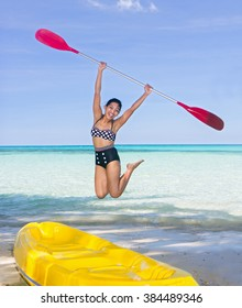 woman with a paddle jumping on the sea beach with kayak