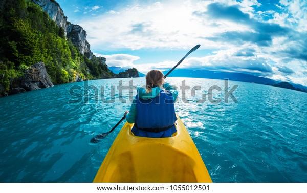 Una mujer rema kayak en el lago con agua turquesa. Patagonia, Chile