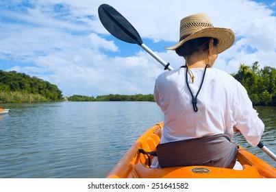 Woman paddles a kayak on a river