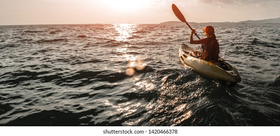 Woman paddles kayak in the sea at sunset