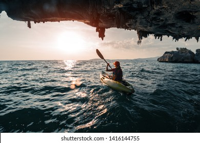 Woman paddles kayak in the tropical sea at sunset and passes the limestone mountains with stalactites