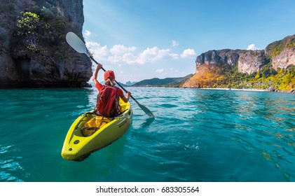 Woman paddles kayak in the tropical sea