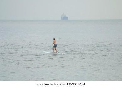 Woman paddling alone doing Sup Paddle in Ilhabela, Brazil.