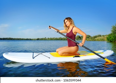 Woman paddling along the river sitting on her knees on the sup board