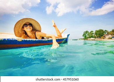 woman paddling in a boat in a paradise island