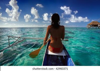 Woman paddling canoe in Tahiti