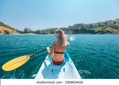 Woman paddling a kayak by the tropical beach. Kayaking tour in Phuket, Thailand